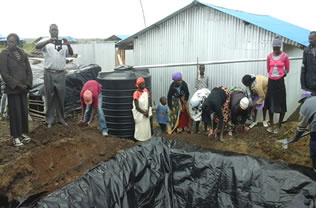 A beneficiary sets up her 2300lts water tank and a dam liner of 18000lts capacity