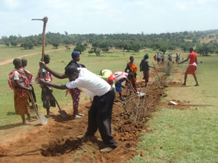 Beneficiaries of the water project participate in digging trenches to Lay pipes for a gravity flow water project.